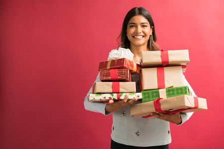 Photo for Attractive young female brunette with Christmas gifts against plain background - Royalty Free Image