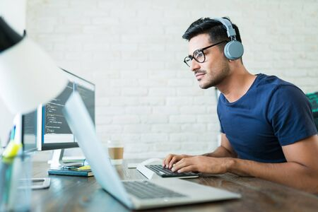 Photo for Handsome young male software developer programming codes while working from home - Royalty Free Image