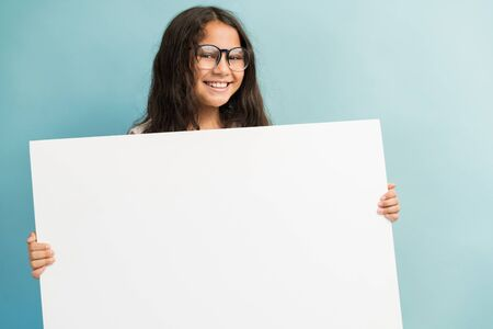 Photo for Portrait of smiling female child with long brown hair holding blank white placard in studio - Royalty Free Image