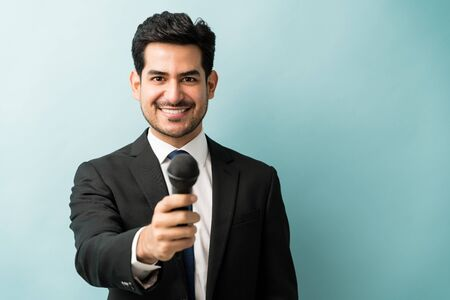 Photo pour Happy good looking male professional in suit giving microphone while standing in studio - image libre de droit
