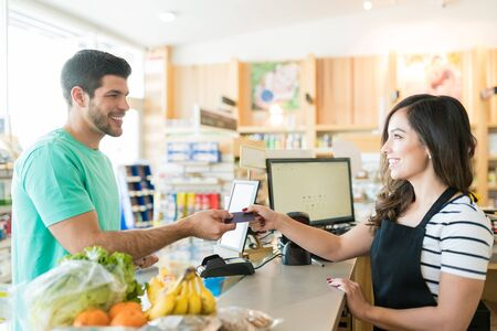Photo pour Smiling female cashier with buyer at checkout counter in grocery store - image libre de droit