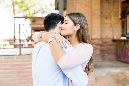 Photo pour Smiling girlfriend embracing boyfriend outside cafe - image libre de droit