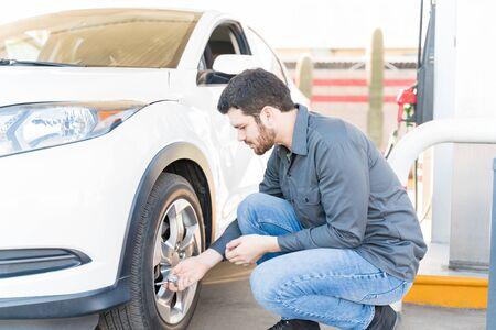 Photo pour Side view of male gas station attendant checking air pressure of car tire - image libre de droit