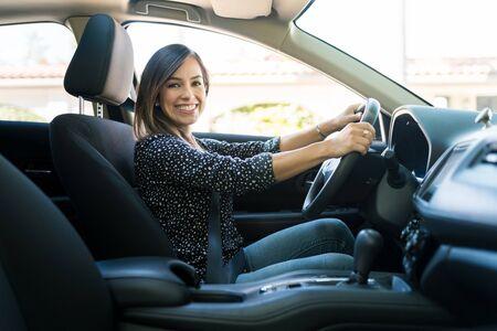 Photo pour Side view of smiling Caucasian woman traveling in new car - image libre de droit
