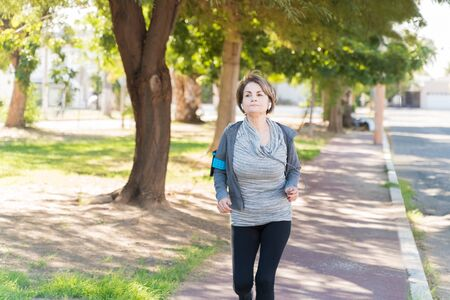 Photo pour Active elderly Caucasian woman running on sidewalk while looking away in city - image libre de droit