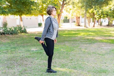 Foto de Full length of active woman stretching her leg while looking away at park - Imagen libre de derechos