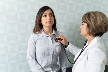 Photo pour Senior physician checking female patient with stethoscope in clinic - image libre de droit