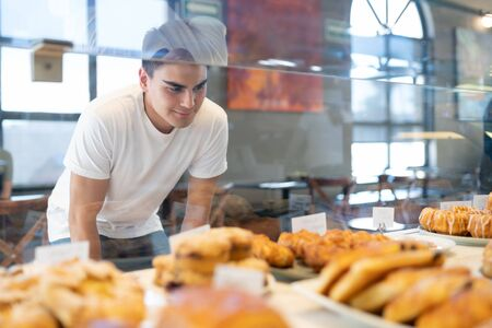 Photo pour Attractive Hispanic man looking through a glass and choosing some bread and pastries in a bakery shop - image libre de droit