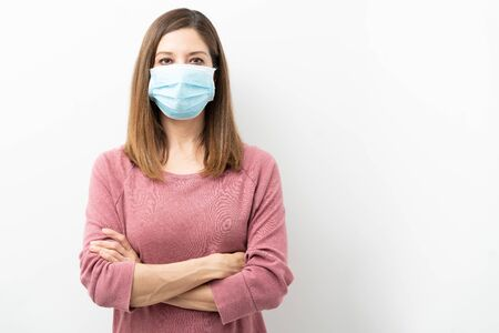 Photo pour Woman in her 40s wearing a surgical mask with arms crossed during coronavirus covid19 pandemic - image libre de droit
