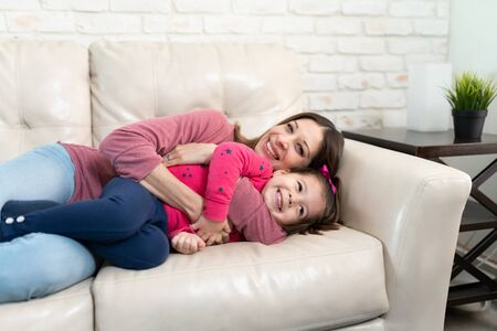 Photo pour Portrait of a beautiful family of mom and daughter embracing and cuddling in a couch at home - image libre de droit