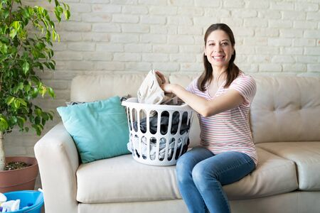 Photo pour Good looking brunette woman doing chores in her house and getting ready to do the laundry - image libre de droit