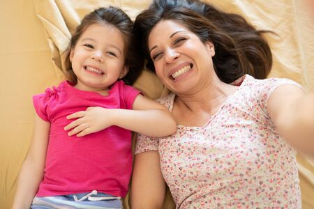 Photo pour Portrait of a Caucasian mother and daughter taking a selfie while having fun and relaxing in bed - image libre de droit
