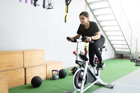 Photo pour Determined Latin young woman cycling in fitness studio during cross-training - image libre de droit