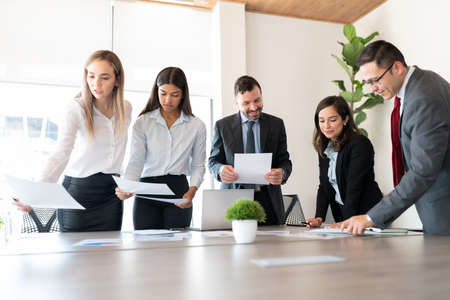 Photo pour Group of male and female business associates with financial data reports during a meeting in office board room - image libre de droit