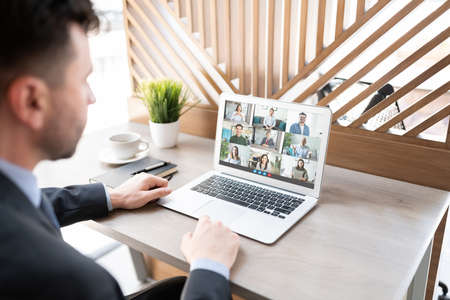 Photo for Rear view of a mature businessman having a conference video call on laptop at his workplace - Royalty Free Image