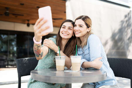 Photo for LGBT couple taking a selfie with a smartphone while sitting in a table outside a coffee shop - Royalty Free Image