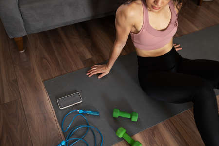 Foto für Strong woman in her 20s wearing activewear sitting in an exercise mat and preparing her home workout with dumbbells and a jump rope - Lizenzfreies Bild