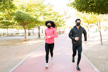 Photo for Young man and young woman with a healthy lifestyle running outdoors during the coronavirus pandemic. Fit couple wearing face masks and jogging in the park - Royalty Free Image