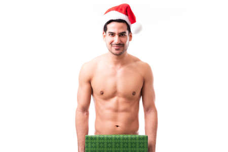 Foto de Portrait of a handsome and confident Hispanic naked man covering with a Christmas present and wearing santa's hat in a studio - Imagen libre de derechos