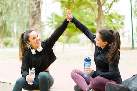 Photo for Excited fit young women in sportswear doing a high five and laughing. Happy best friends resting and celebrating finishing their cardio workout - Royalty Free Image