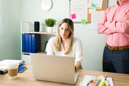 Photo pour Upset male boss standing next to a female coworker and checking her work. Beautiful caucasian woman working and typing on a laptop at the office desk - image libre de droit