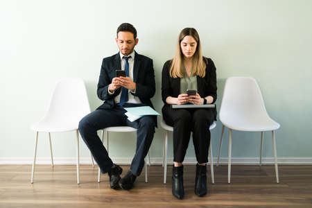 Photo pour Professional business woman and man looking at their smartphones and texting while waiting for a job interview while sitting in a recruitment office - image libre de droit