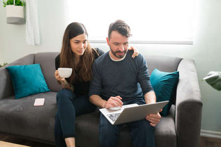 Photo pour Loving wife hugging her husband while drinking coffee in the morning at home. Hispanic man showing an attractive woman his online shopping on the laptop - image libre de droit