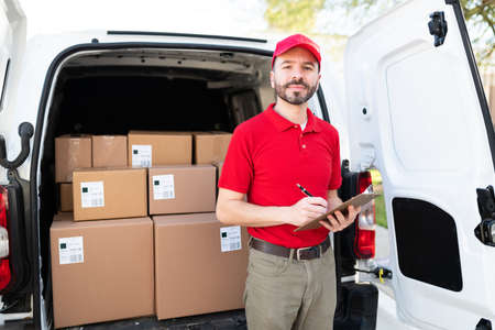 Photo for Handsome latin man wearing a red uniform and standing in the back of a white van. Delivery man making eye contact while holding a clipboard and a pen - Royalty Free Image
