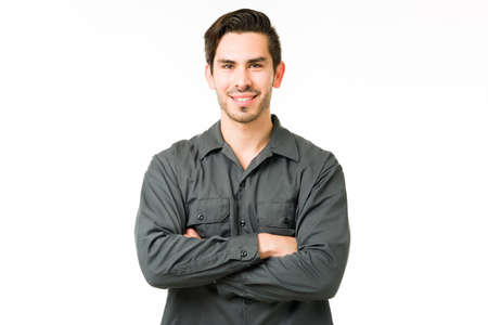 Photo pour Handsome young man smiling while standing in front of a white background. Hispanic handyman with his arms crossed and making eye contact - image libre de droit