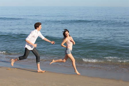 Couple playing and running on the beach shore near the water