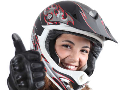 Happy biker woman with a motocross helmet and thumb up isolated on a white background