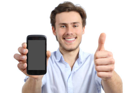 Young man showing a blank screen smart phone with thumbs up isolated on a white background