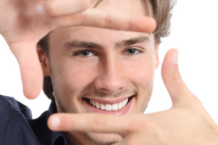 Man with perfect white smile framing face with hands on a white background