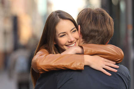 Portrait of a happy couple hugging in the street with the woman face in foreground