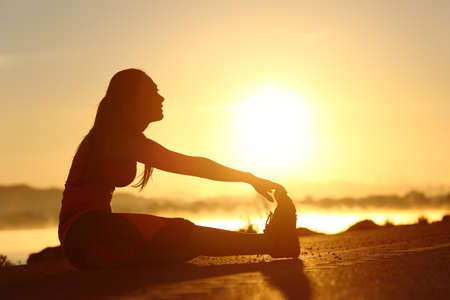 Silhouette of a fitness woman stretching at sunset with the sun in the backgroundの写真素材
