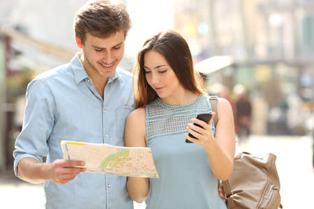 Couple of tourists consulting a city guide and mobile phone gps in a street