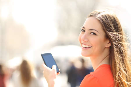Happy woman smiling and walking in the street using a smartphone and looking at camera