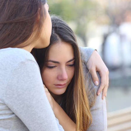 Sad girl crying and a friend comforting her outdoors in a park