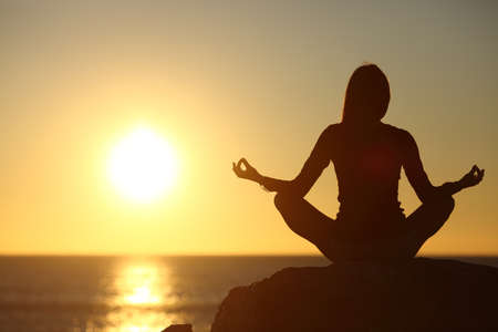 Woman meditating and practicing yoga watching the sun on the beach at sunset