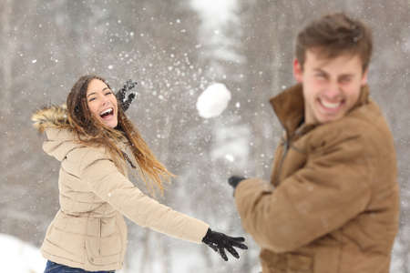 Couple playing with snow and girlfriend throwing a ball in winter holidays
