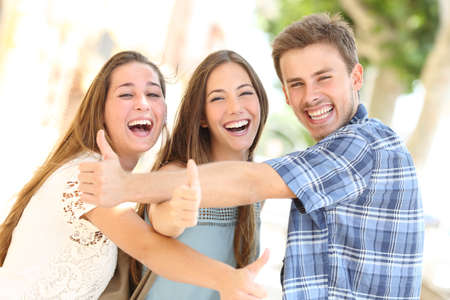 Three happy teenagers laughing with thumbs up looking at you in the street