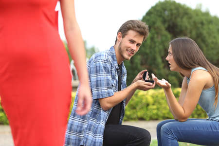 Amazed unfaithful man looking another girl during marriage proposal and his girlfriend is angry