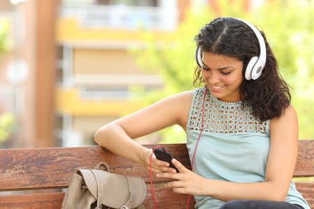 Woman listening to the music from a smart phone with headphones in a park