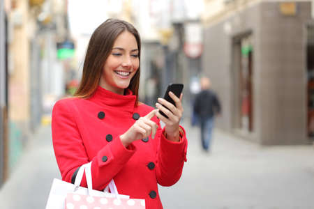 Shopper woman buying online on the smart phone in the street