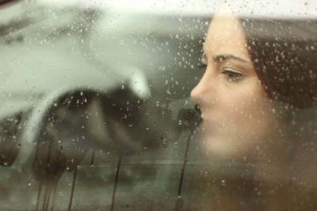 Sad woman or teenager girl looking through a steamy car windowの写真素材
