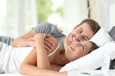 Happy couple flirting in the morning on the bed at home