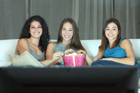 Three happy friends watching tv sitting on a couch at home