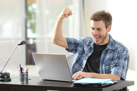 Euphoric winner happy man using a laptop in a desk at home
