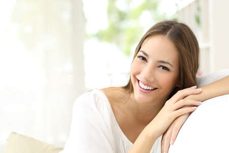 Beauty woman with white perfect smile looking at camera at homeの写真素材