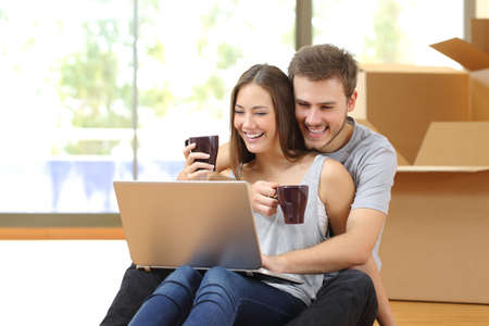 Couple buying online with a laptop and moving house sitting on the floor